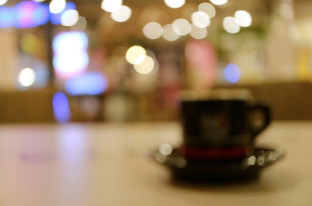 Image floue d'une tasse de boisson chaude sur une table en bois dans le café avec des lumières de bokeh