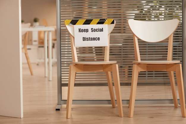 Image de fond de chaises en bois pour attendre en ligne au bureau avec signe de garder la distance sociale, espace de copie