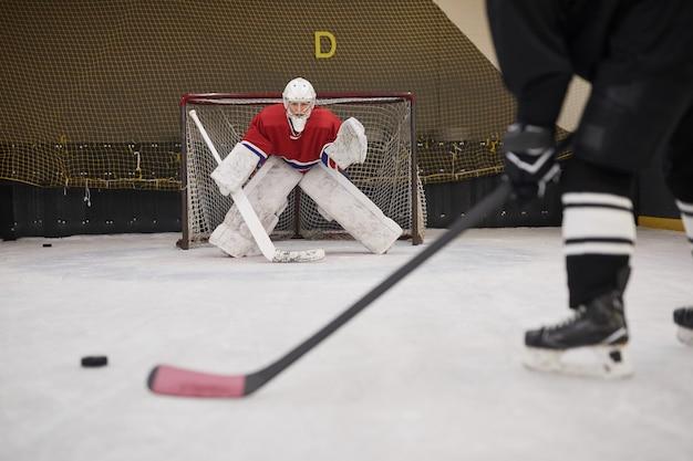 Image de fond du gardien de but de hockey prêt à défendre la porte en patinoire