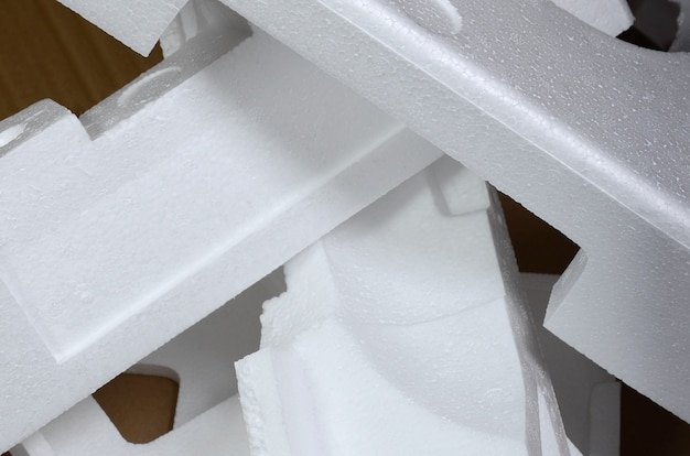 Image de fond avec du papier carton beige et des boîtes en polystyrène rejetés comme déchets.
