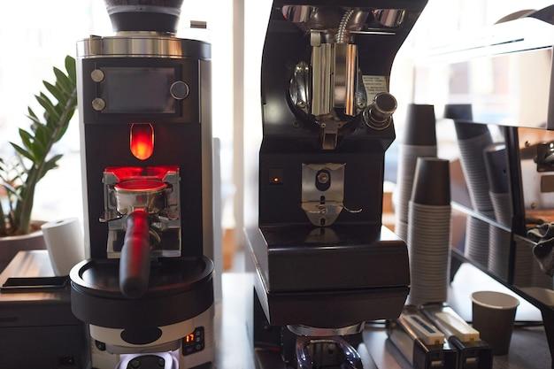 Image de fond des machines à café et des gobelets en papier dans un café ou un café, espace pour copie