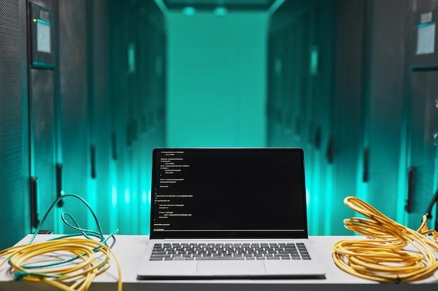Image de fond d'un ordinateur portable avec code à l'écran dans la salle des serveurs, espace de copie
