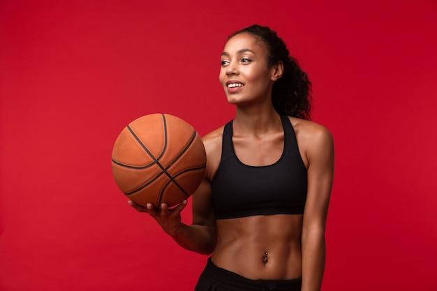 Image d'un fort jeune joueur de basket-ball femme fitness sports africains posant isolé sur mur rouge mur holding ball.