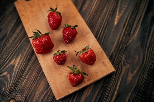 Image de fraises rouges fraîches sur planche de bois