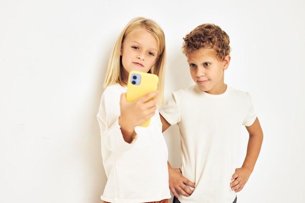 Image d'un garçon et d'une fille souriant avec un téléphone à la main fond clair de mode