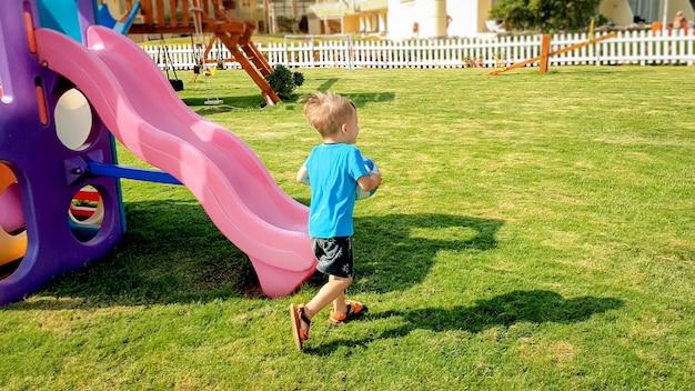 Image d'un garçon joyeux riant tenant un ballon de football dans les mains et courant sur une aire de jeux pour enfants au parc