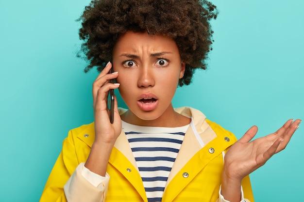Image de gestes de femme afro-américaine frustrés avec paume pendant la conversation téléphonique, regarde avec indignation, vêtu d'un imperméable imperméable, isolé sur bleu, exprime l'aversion
