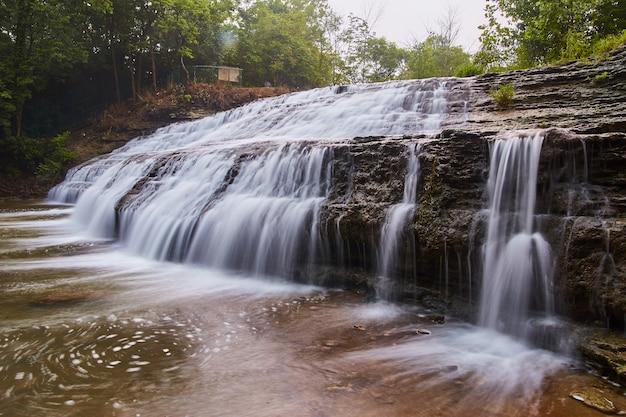 Image d'une grande cascade en cascade sur des ardoises et des falaises rocheuses