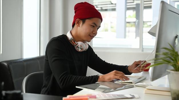 L'image d'un graphiste créatif masculin utilise la sélection des couleurs et travaille sur ordinateur sur le lieu de travail avec des outils de travail et des accessoires.
