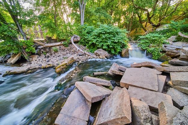 Image de gravats de blocs de ciment entourant la rivière avec une petite cascade et une forêt verte luxuriante