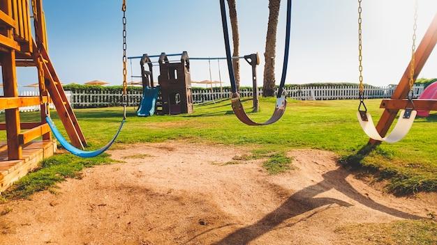 Image en gros plan de balançoires vides sur l'aire de jeux pour enfants à une belle journée ensoleillée. personne ne joue dans le parc