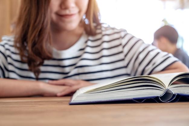 Image gros plan d'une belle femme asiatique lisant un livre sur une table en bois