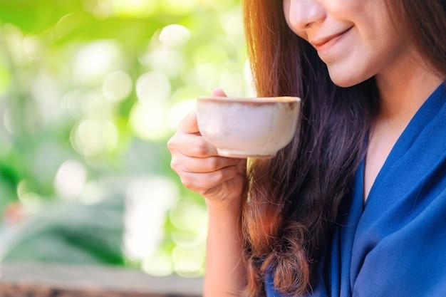 Image en gros plan d'une belle femme asiatique tenant et buvant du café chaud dans le jardin