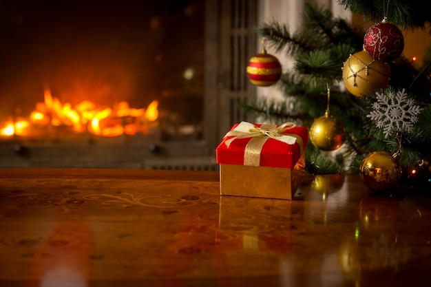 Image en gros plan d'une boîte-cadeau rouge sur une table en bois devant une cheminée en feu et un arbre de noël