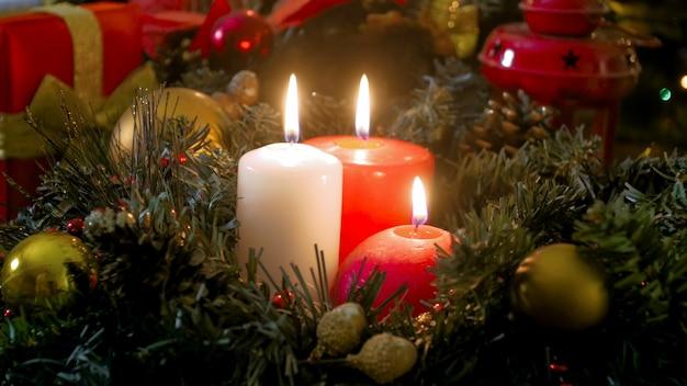 Image en gros plan de bougies de noël brûlantes rouges et blanches sur la couronne de l'avent
