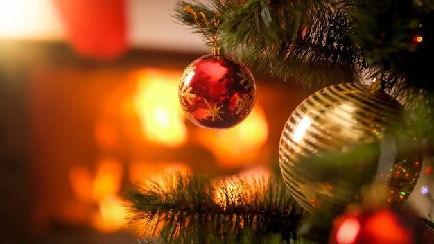 Image gros plan de boules de noël rouges et dorées accrochées à l'arbre de noël contre le feu brûlant dans la cheminée