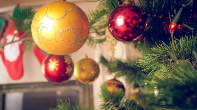 Image gros plan de boules rouges et dorées accrochées à l'arbre de noël
