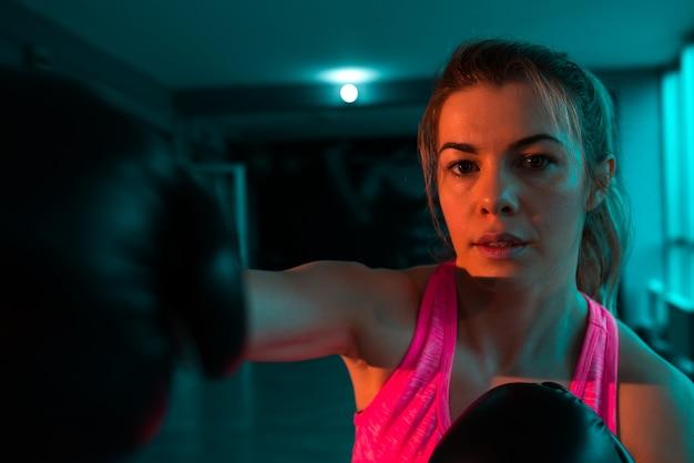 Image gros plan de la boxeuse féminine poinçonnant.
