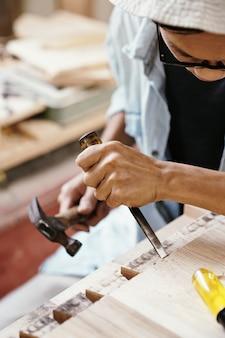 Image en gros plan d'un charpentier travaillant avec du bois dur, il utilise un marteau et un ciseau