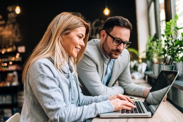 Image gros plan de deux jeunes attrayants ayant une réunion d'affaires dans un café moderne.