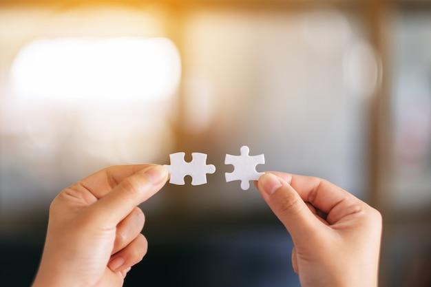 Image en gros plan de deux mains tenant et assemblant un morceau de puzzle blanc