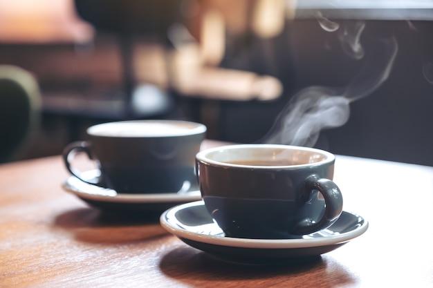Image gros plan de deux tasses bleues de café latte chaud et café americano sur table en bois vintage au café