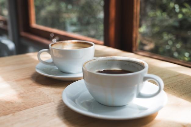 Image gros plan de deux tasses de café blanc sur une table en bois