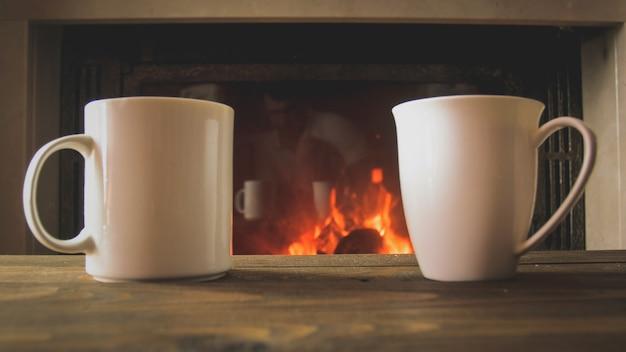 Image en gros plan de deux tasses de thé sur une table en bois à côté d'une cheminée en feu