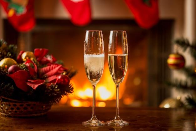 Image en gros plan de deux verres de champagne devant une cheminée en feu