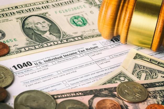 Image en gros plan du formulaire de déclaration d'impôt sur le revenu individuel américain 1040 avec de l'argent en dollars américains, des pièces de monnaie et un marteau de juge.