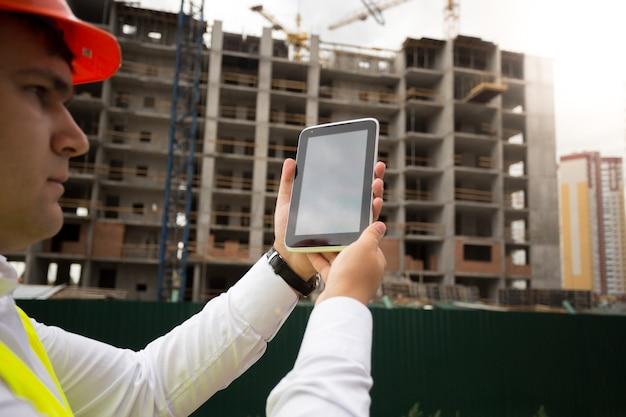 Image en gros plan du jeune ingénieur en construction sur chantier à l'aide d'une tablette numérique