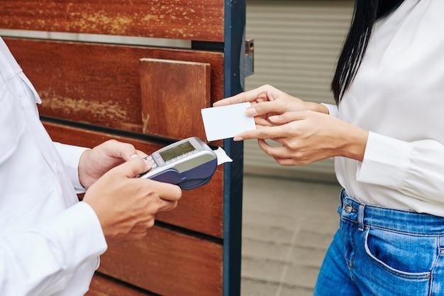 Image en gros plan du livreur donnant le terminal de paiement à la cliente avec carte de crédit