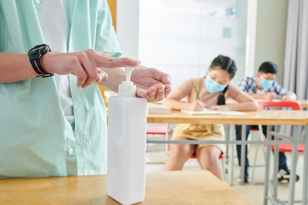 Image en gros plan d'écolier appliquant un désinfectant pour les mains pendant la leçon, ses camarades de classe dans des masques médicaux écrivant dans les manuels