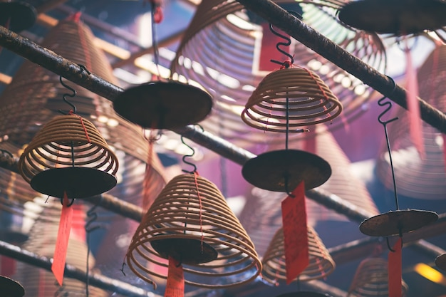 Image en gros plan d'encens en spirale suspendus au plafond dans un temple chinois
