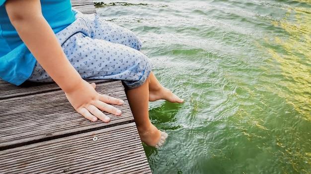 Image en gros plan d'un enfant assis sur la jetée en bois du fleuve et tenant les pieds dans l'eau. enfants jouant et éclaboussant l'eau avec des jambes