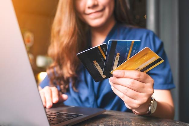 Image en gros plan d'une femme d'affaires détenant des cartes de crédit tout en utilisant un ordinateur portable