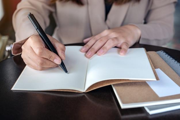 Image gros plan d'une femme d'affaires écrit sur un cahier vierge sur une table en bois