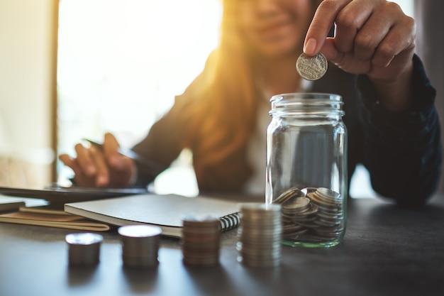 Image en gros plan d'une femme d'affaires empilant et mettant des pièces dans un bocal en verre