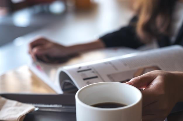 Image gros plan d'une femme d'affaires lisant un livre avec une tasse de café sur la table à café