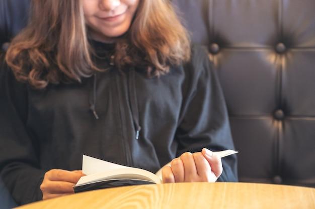 Image gros plan d'une femme asiatique tenant et lisant un livre sur la table en bois