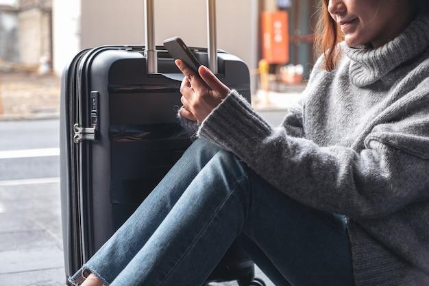 Image gros plan d'une femme assise et utilisant un téléphone mobile avec un bagage noir pour voyager