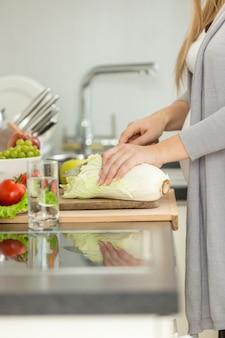 Image gros plan d'une femme coupant du chou frais pour la soupe