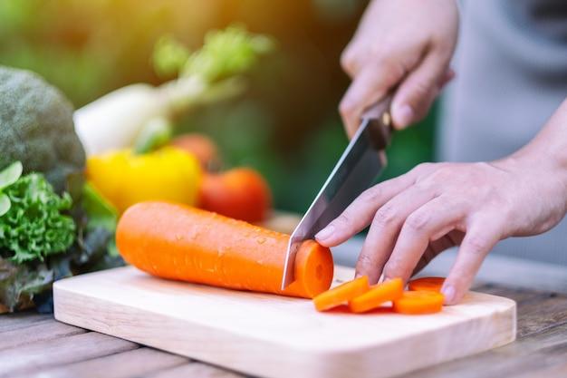 Image en gros plan d'une femme coupant et hachant des carottes au couteau sur une planche de bois