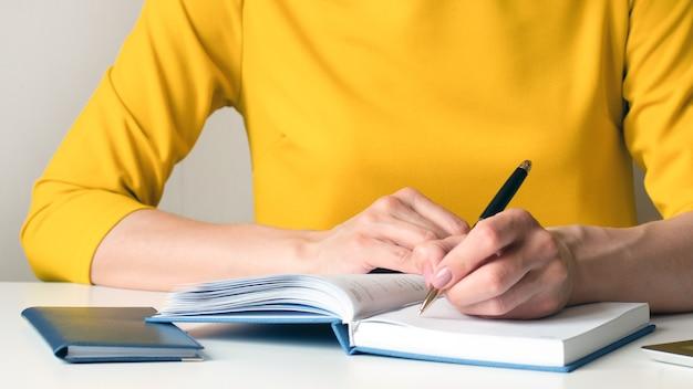 Image en gros plan d'une femme dans une robe jaune assis à un bureau et écrire quelque chose dans un cahier vierge blanc