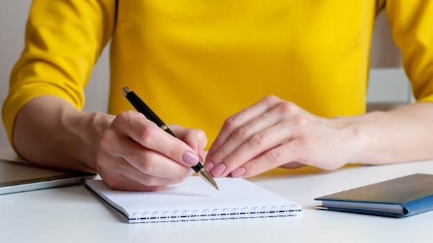 Image gros plan d'une femme écrivant sur un cahier vierge blanc