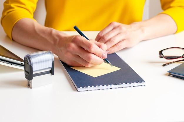 Image gros plan d'une femme écrivant sur une carte de papier jaune