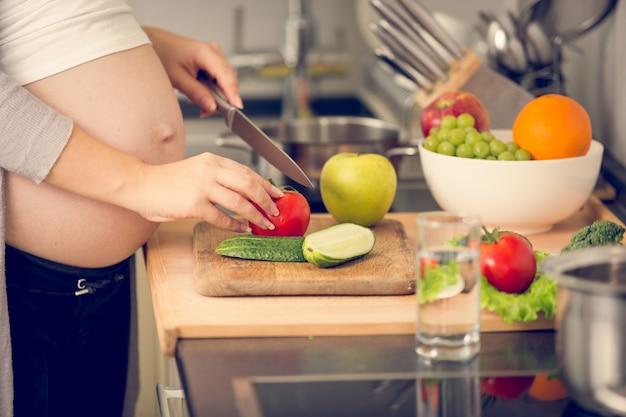 Image gros plan d'une femme enceinte coupant des légumes sur une planche de bois