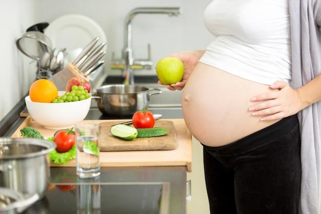 Image gros plan d'une femme enceinte préparant le dîner dans la cuisine