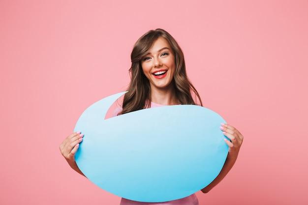 Image gros plan de femme européenne souriante tenant une bulle de pensée bleue vierge avec fond pour le texte dans ses mains, isolé sur fond rose
