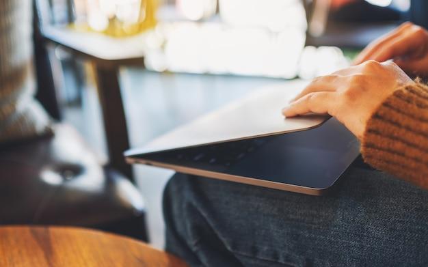 Image en gros plan d'une femme fermer ou ouvrir un ordinateur portable